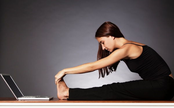 Woman stretching in fornt of laptop.
